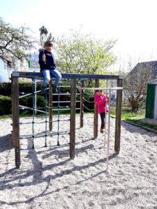 Ein Junge und ein Mädchen spielen auf einem Klettergerüst.