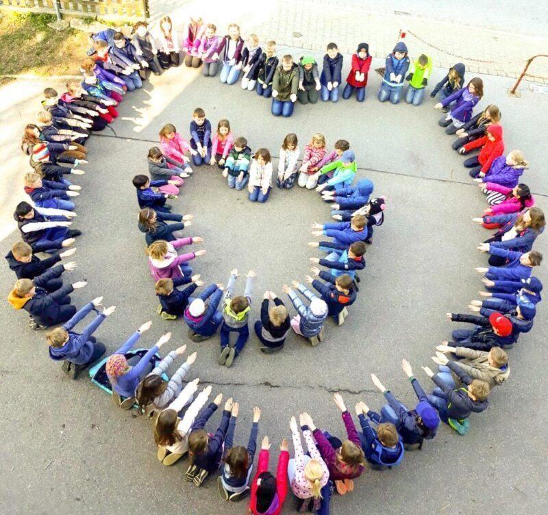 Die Kinder der Grundschule bilden sitzend zwei ineinander liegende Herzen.